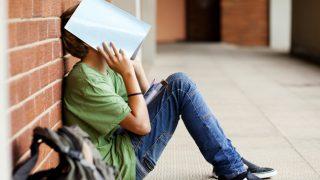 iskolás fiú (iskolás fiú, iskola, tanulás, gyerek, fiú, szomorú, depresszió, rossz kedv)