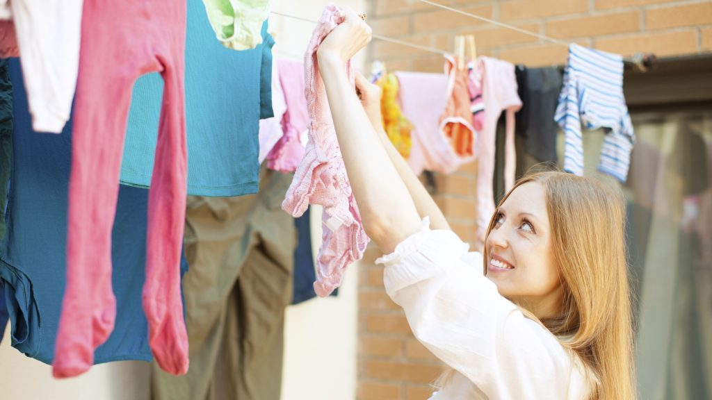 Positive girl drying clothes on clothesline