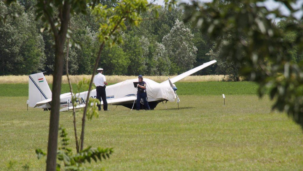 Pusztaszer, 2014. július 2. Rendõrök helyszínelnek a pusztaszeri repülõtéren 2014. július 2-án egy kisrepülõgép mellett, amely manõver közben elsodort egy 18 éves nõt. A fiatal nõt a repülõgép egyik kereke találta fejen, életveszélyes sérüléseket szenvedett. MTI Fotó: Donka Ferenc