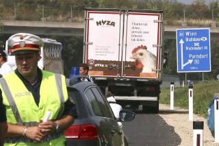 Parndorf, 2015. augusztus 27.Rendőrök egy teherautó mellett az A4-es autópályán Pandorf közelében 2015. augusztus 27-én. A teherautóban menekültek holttestére bukkantak.  Egyes sajtóértesülések szerint akár az ötvenet is elérheti a halottak száma. (MTI/AP/Ronald Zak)