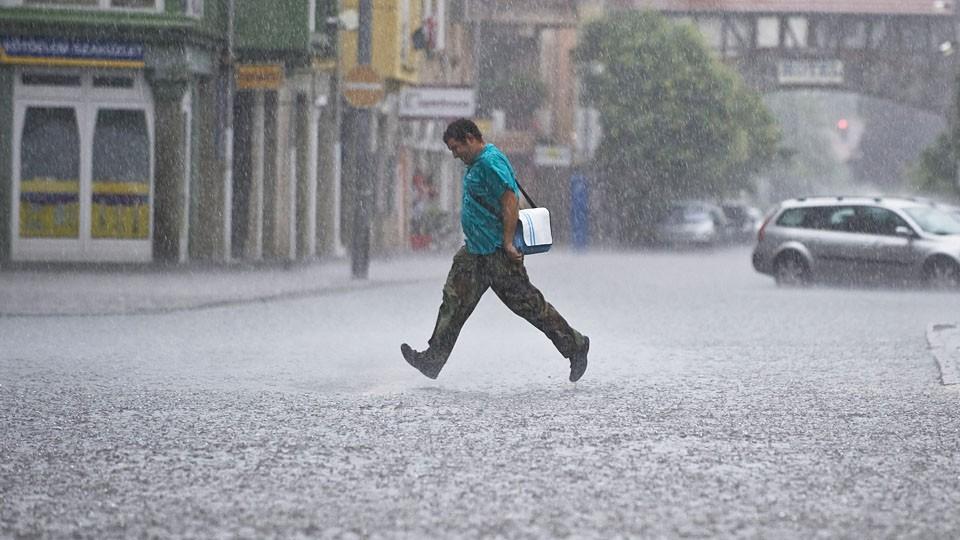 Kecskemét, 2011. július 29.Egy férfi szalad az esőben Kecskeméten, a Petőfi Sándor utca és a Kőhíd utca kereszteződésében, amely útszakaszt elöntött a hírtelen lezúduló csapadék.MTI Fotó: Ujvári Sándor