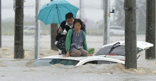 Dzsoszo, 2015. szeptember 10. Az autójuk tetején segítségre váró helyiek a heves esõzések által elöntött Dzsoszo egyik utcáján, Ibaraki prefektúrában 2015. szeptember 10-én. A két napja tartó felhõszakadás miatt a szigetország középsõ részén néhol 50 centiméternyi esõ esett, a rengeteg víz több helyen áradást okozott és földcsuszamlást. A hatóság 90 ezer embert utasított otthona elhagyására Tocsigi prefektúra legveszélyeztetettebb területein. (MTI/AP/Kyodo News)