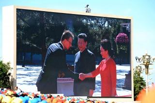Peking, 2015. szeptember 3.A pekingi Tiananmen téren elhelyezett kivetítőn Szijjártó Péter külgazdasági és külügyminiszter kezet fog (b) Hszi Csin-ping kínai elnök (k) nejével, Peng Li-jüannal 2015. szeptember 3-án, a Kína Japánnal szemben az 1930-as, 1940-es években folytatott ellenálló háborújának, egyben a II. világháború végének a 70. évfordulója alkalmából rendezett megemlékezésen.MTI Fotó: Trebitsch Péter