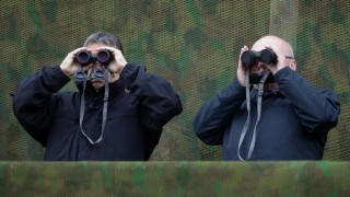 """Hungarian Prime Minister Viktor Orban (L) and Defence Minister Csaba Hende (R) look through binoculars during a joint Hungarian-US military exercise near Osku village, Hungary on October 2, 2014 on October 2, 2014.Hungarian and US soldiers took part in a joint military exercise Thursday, simulating """"everyday"""" battle situations in Ukraine. AFP PHOTO / ATTILA KISBENEDEK"""