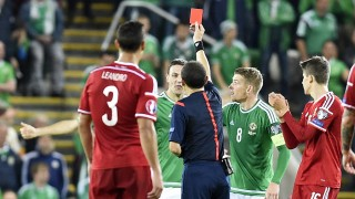 Northern Ireland's defender Chris Baird (2nd L) receives a red card from referee Cuneyt Cakir during the Euro 2016 qualifying group F football match between Northern Ireland and Hungary at Windsor Park in Belfast on September 7, 2015. Kyle Lafferty's priceless late equaliser kept Northern Ireland within touching distance of an historic berth at Euro 2016 as the 10-man hosts rescued a 1-1 draw against Hungary on Monday. AFP PHOTO / MICHAEL COOPER