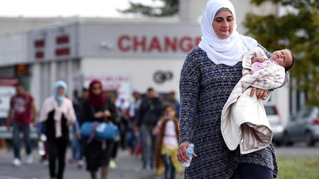 A migrant mother crosses the border between Hungary and Austria on September 10, 2015 near Nickelsdorf, Austria. Thousands of migrants have continued to cross into Hungary over the last few days from Serbia. Since the beginning of 2015 the number of migrants using the so-called 'Balkans route' has exploded with migrants arriving in Greece from Turkey and then travelling on through Macedonia and Serbia before entering the EU in Hungary from where they continue via Austria to Germany . The number of people leaving their homes in war torn countries such as Syria, marks the largest migration of people since World War II. AFP PHOTO/JOE KLAMAR