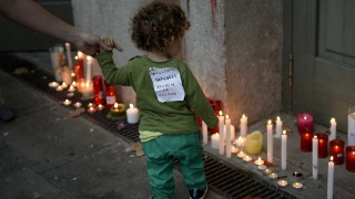 """TOPSHOTS A boy with a sign on his clothe rewading """"Welcome refugees, stop the war"""" passes by candles during a candle light tribute to migrants from Syria, in a Barcelona's train station, on September 4, 2015. More than 350,000 migrants have risked their lives crossing the Mediterranean this year, and some 2,600 have died while making the perilous journey to Europe, the International Organisation for Migration said on September 1, 2015.    AFP PHOTO/ JOSEP LAGO"""