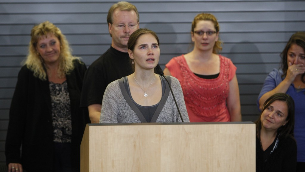 Surrounded by family members Amanda Knox makes a few comments during a news conference shortly after her arrival at Seattle-Tacoma International Airport October 4, 2011, in Seattle.  US student Amanda Knox arrived home a day after she was acquitted of murder and sexual assault charges and freed from jail in Italy, after a four-year ordeal.    AFP PHOTO / Kevin CASEY