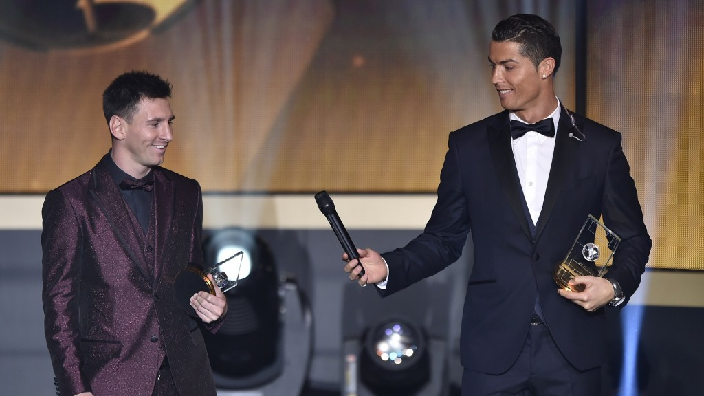 Real Madrid and Portugal forward Cristiano Ronaldo hands a microhpone to Barcelona and Argentina forward Lionel Messi (L) as they stand on stage after being selected in the 2014 FIFA FIFPro World XI during the FIFA Ballon d'Or award ceremony at the Kongresshaus in Zurich on January 12, 2015. AFP PHOTO / FABRICE COFFRINI