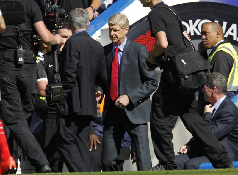 Arsenal's French manager Arsene Wenger (C) shakes hands with Chelsea's Portuguese manager Jose Mourinho ahead of the English Premier League football match between Chelsea and Arsenal at Stamford Bridge in London on September 19, 2015. AFP PHOTO / IAN KINGTON   RESTRICTED TO EDITORIAL USE. No use with unauthorized audio, video, data, fixture lists, club/league logos or 'live' services. Online in-match use limited to 75 images, no video emulation. No use in betting, games or single club/league/player publications.