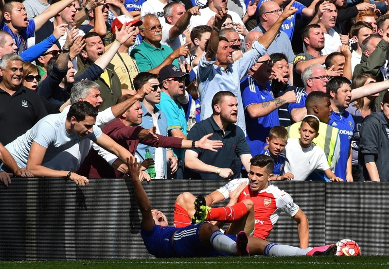 Chelsea's Belgian midfielder Eden Hazard clashes with Arsenal's Brazilian defender Gabriel as the Chelsea fan react during the English Premier League football match between Chelsea and Arsenal at Stamford Bridge in London on September 19, 2015. AFP PHOTO / BEN STANSALL   RESTRICTED TO EDITORIAL USE. No use with unauthorized audio, video, data, fixture lists, club/league logos or 'live' services. Online in-match use limited to 75 images, no video emulation. No use in betting, games or single club/league/player publications.