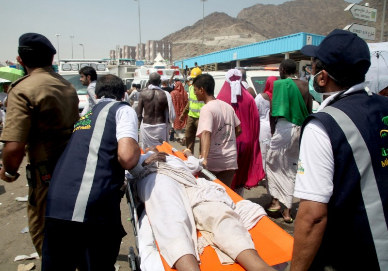 Saudi emergency personnel transport a Hajj pilgim on a stretcher at the site where at least 450 were killed and hundreds wounded in a stampede in Mina, near the holy city of Mecca, at the annual hajj in Saudi Arabia on September 24, 2015. The stampede, the second deadly accident to strike the pilgrims this year, broke out during the symbolic stoning of the devil ritual, the Saudi civil defence service said. AFP PHOTO / STR