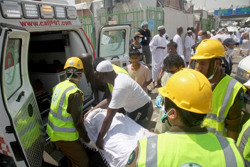 Saudi emergency personnel and Hajj pilgrims load a wounded person into an ambulance at the site where at least 450 were killed and hundreds wounded in a stampede in Mina, near the holy city of Mecca, at the annual hajj in Saudi Arabia on September 24, 2015. The stampede, the second deadly accident to strike the pilgrims this year, broke out during the symbolic stoning of the devil ritual, the Saudi civil defence service said. AFP PHOTO / STR