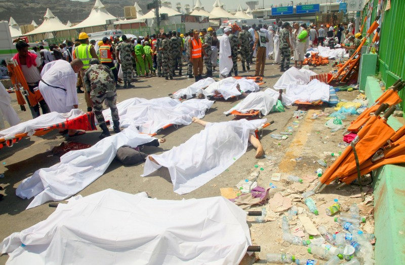 Saudi emergency personnel and Hajj pilgrims stand near bodies covered in sheets at the site where at least 450 were killed and hundreds wounded in a stampede in Mina, near the holy city of Mecca, at the annual hajj in Saudi Arabia on September 24, 2015. The stampede, the second deadly accident to strike the pilgrims this year, broke out during the symbolic stoning of the devil ritual, the Saudi civil defence service said. AFP PHOTO / STR