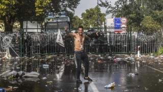 A refugee reacts after Hungarian riot police use water cannon to push back refugees at the Hungarian border with Serbia near the town of Horgos on September 16, 2015. Europe's 20-year passport-free Schengen zone appeared to be a risk of crumbling with Germany boosting border controls on parts of its frontier with France as migrants desperate to find a way around Hungary's border fence began crossing into Croatia. With a string of EU countries tightened frontier controls in the face of the unprecedented human influx, the cherished principle of free movement across borders -- a pillar of the European project -- seemed in grave jeopardy. AFP PHOTO / ARMEND NIMANI