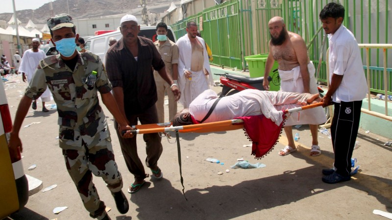 TOPSHOTS Hajj pilgrims and Saudi emergency personnel carry a woman on a stretcher at the site where at least 450 were killed and hundreds wounded in a stampede in Mina, near the holy city of Mecca, at the annual hajj in Saudi Arabia on September 24, 2015. The stampede, the second deadly accident to strike the pilgrims this year, broke out during the symbolic stoning of the devil ritual, the Saudi civil defence service said. AFP PHOTO / STR