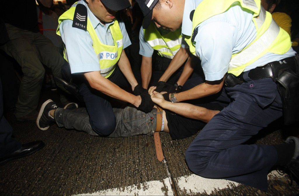 Mods who turn on pro-democracy protesters and students are arrested by anti-triad police at Hong Kong's shopping Mongkok district, where a main road is occupied, October 3, 2014. Violent scuffles broke out in one of Hong Kong?s most famous and congested shopping districts on Friday, as supporters of Chinese rule stormed tents and ripped down banners belonging to pro-democracy protesters. In the gritty, bustling district of Mongkok ? considered one of the most crowded places on Earth with its high-rise apartment blocks packed closely together over neon lights, bars, restaurants and open-air markets ? about 1,000 Beijing supporters clashed with about 100 protesters on Friday, spitting and throwing water bottles. Hong Kong?s mass pro-democracy protests had ebbed on Friday morning after the chief executive offered talks to student representatives minutes before their midnight deadline for his resignation. (EyePress/Sunny Mok)