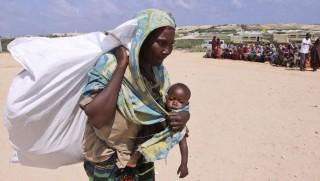 Mogadishu, 2011. szeptember 1. Egy szomáliai asszony az ENSZ menekültügyi szervezete, az UNHCR által kiosztott élelmiszersegélyt visz a szomáliai fõvárosban, Mogadishuban kialakított ideiglenes menekülttáborban 2011. augusztus 31-én. Az Afrika szarván pusztító szárazság miatt kialakult éhínség miatt Szomália déli részeibõl tömegesen menekülnek az emberek északra, Mogadishuba és délre, a szomszédos Kenyába. (MTI/AP/Halíl Szenoszi)