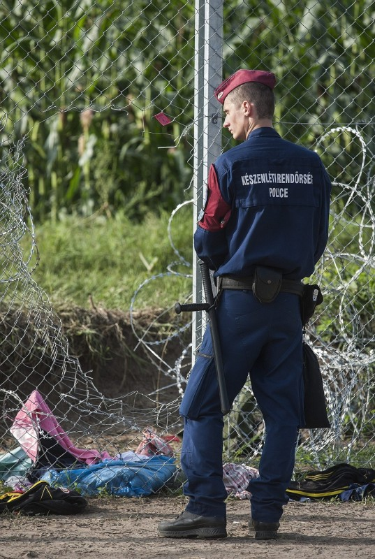 Röszke, 2015. szeptember 15. Rendõr a mûszaki határzárnál, amelyet illegális bevándorlók megrongálták a röszkei átkelõhöz közel 2015. szeptember 15-én. A 16 tagú csoport tagjai elõször a gyorstelepítésû drótakadályt, majd a három méter magas drótkerítést is átvágták, és átmásztak azon. A rendõrök elfogták, majd elõállították õket. Ezen a napon hatályba léptek a migrációs helyzet miatti új szabályozások. MTI Fotó: Máthé Zoltán