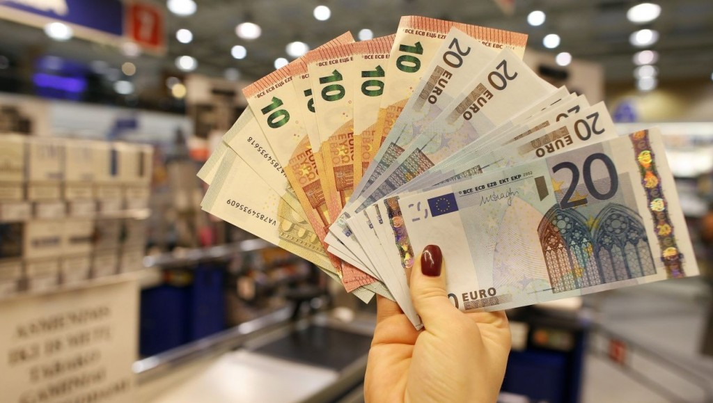 Vilnius, 2015. január 1. Egy bolti eladó mutatja a tíz és húszeurós bankjegyeket Vilniusban 2015. január 1-jén. Litvánia ezen a napon csatlakozott az eurózónához. (MTI/AP/Mindaugas Kulbis)