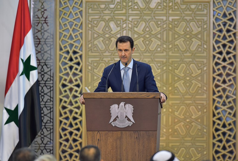 """A handout picture released on July 26, 2015 by the official Syrian Arab News Agency (SANA) shows President Bashar al-Assad delivering a speech in the capital Damascus. Al-Assad acknowledged the shrinking ranks of his government's army in a rare public speech, but insisted the force was still capable of beating rebel fighters. AFP PHOTO / HO /SANA== RESTRICTED TO EDITORIAL USE - MANDATORY CREDIT """"AFP PHOTO / HO /SANA"""" - NO MARKETING NO ADVERTISING CAMPAIGNS - DISTRIBUTED AS A SERVICE TO CLIENTS =="""