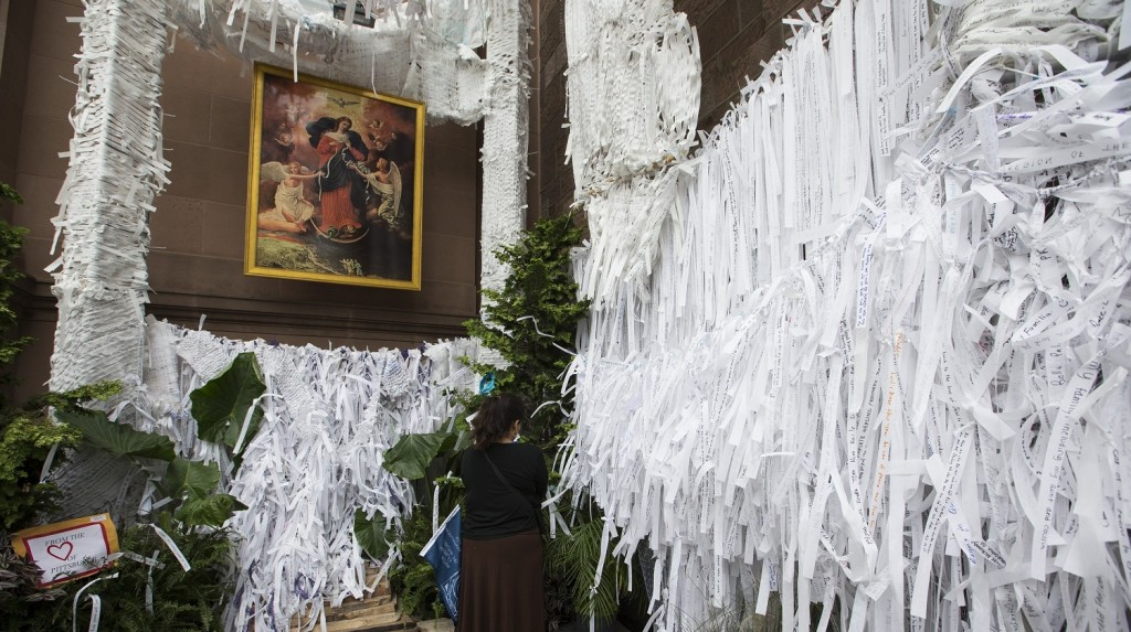 PHILADELPHIA, USA - SEPTEMBER 27: A woman adds her prayer to the thousands left on strips of paper at the Knotted Grotto at the Cathedral Basilica of Saints Peter and Paul during Pope Francis' visit to Philadelphia, USA on September 27, 2015. Visitors write personal prayers on the strips of paper and then take another persons prayer after leaving theirs. Samuel Corum / Anadolu Agency