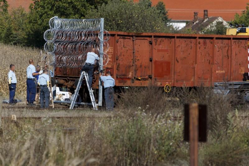Zákány, 2015. szeptember 23. Büntetés-végrehajtási dolgozók szögesdrótot szerelnek egy vasúti kocsira a Gyékényes vasútállomáson, Zákányban 2015. szeptember 23-án.  MTI Fotó: Varga György