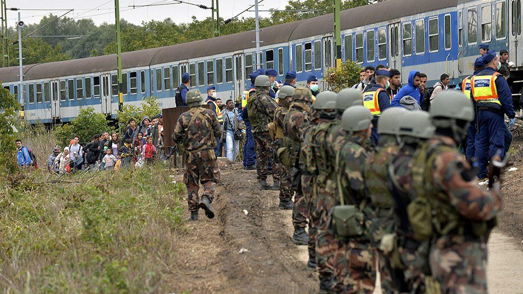 Zákány, 2015. szeptember 26.Migránsok haladnak a rendőrök és katonák sorfala mellett a gyékényesi vasútállomásnál, Zákány közelében 2015. szeptember 26-án.MTI Fotó: Máthé Zoltán