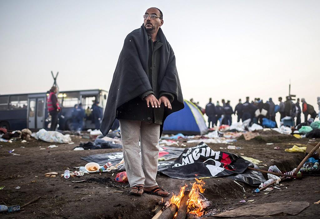 Röszke, 2015. szeptember 13.Egy Illegális bevándorló melegszik a tűznél a röszkei Dugonyi úti rendőrségi gyűjtőponton 2015. szeptember 13-án.MTI Fotó: Mohai Balázs
