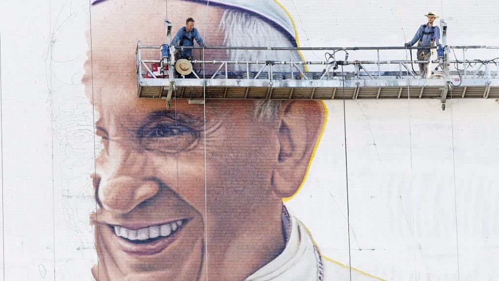New York, 2015. augusztus 28. Festõk dolgoznak Ferenc pápa óriásportréján egy New York-i irodaház falán 2015. augusztus 28-án. A pápa szeptember 22-én kezdi meg ötnapos észak-amerikai körútját, amelynek során látogatást tesz Washingtonban és Philadelphiában, valamint felszólal az ENSZ New York-i székházában. (MTI/AP/Mark Lennihan)