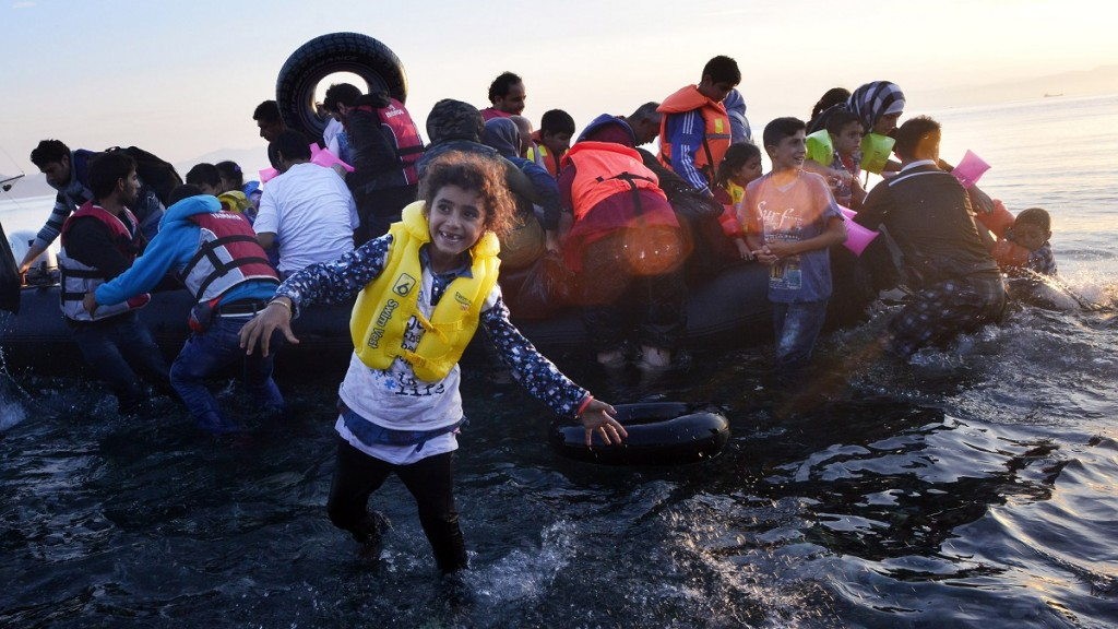 KOS, GREECE - AUGUST 15:  A Syrian child smiles as refugees arrive at a beach on the Greek island of Kos after crossing a part of the Aegean sea from Turkey to Greece in a dinghy on August 15, 2015 in Kos, Greece. The Greek government has sent a cruise ship to the island of Kos which will be able to house up to 2,500 refugees and operate as a registration centre, after 2,000 Syrian refugees were locked in an old stadium during a registration process and left without water for more than a day.  (Photo by Milos Bicanski/Getty Images)