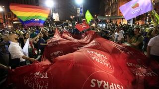 """Athén, 2015. szeptember 21.Az eddig kormányzó baloldali Sziriza párt támogatói ünnepelnek Athénban 2015. szeptember 20-án, miután pártjuk győzött az előre hozott görög parlamenti választásokon. A zászló feliratának jelentése: """"A másik Európa Ciprasszal"""". (MTI/AP/Lefterisz Pitarakisz)"""