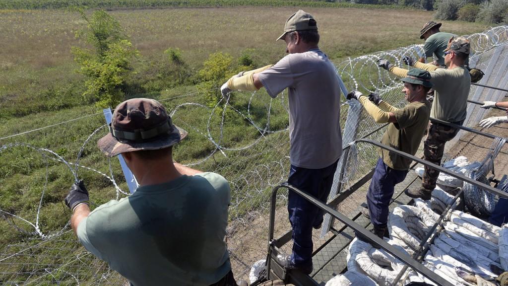 Ásotthalom, 2015. augusztus 30.Katonák dolgoznak az ideiglenes biztonsági határzár építésén a gyorstelepítésű drótakadály mellett Ásotthalomnál 2015. augusztus 30-án. Kiépült a műszaki határzár első szakasza, a drótakadállyal párhuzamosan a teljes szakaszon megépül az ideiglenes biztonsági határzár is.MTI Fotó: Máthé Zoltán