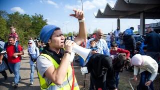 Hegyeshalom, 2015. szeptember 13. Egy tolmács arab nyelven segít tájékoztatni a migránsokat a hegyeshalmi 1-es fõúti határátkelõnél 2015. szeptember 13-án. MTI Fotó: Krizsán Csaba
