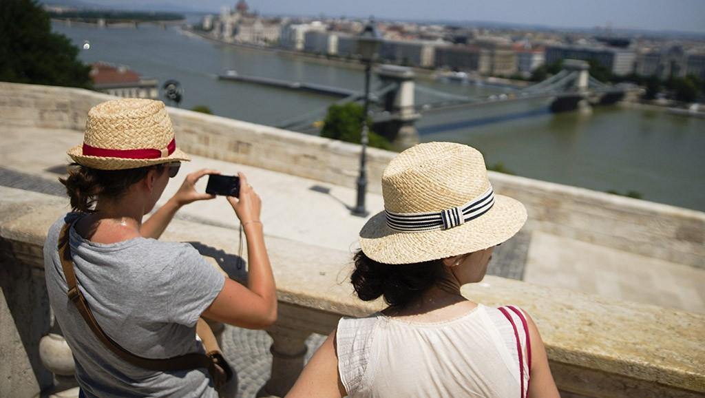 Budapest, 2015. július 6.Szalmakalapot viselnek az erős napsütés ellen fiatal nők a budai Várban 2015. július 6-án. Az országos tiszti főorvos július 4-től július 8-án éjfélig hőségriadót rendelt el, mert ebben az időszakban eléri vagy meghaladja a napi középhőmérséklet a 27 Celsius-fokot.MTI Fotó: Balogh Zoltán