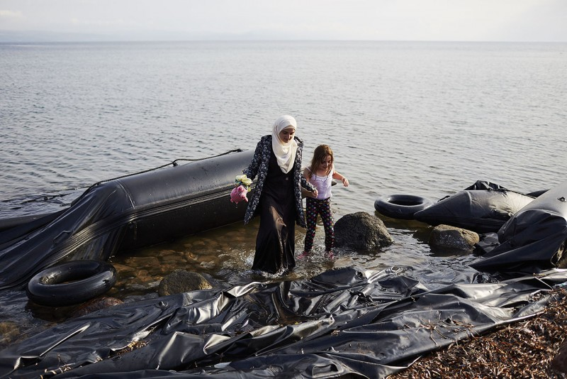 MYTILENE, GREECE - SEPTEMBER 24: Two girls step from a deflated dinghy as refugees and migrants arrive ashore on the Greek island of Lesbos from Turkey as they journey into Europe on September 24, 2015 in Lesbos, Greece. Migrants continue to make the dangerous sea crossing ahead of the onset of Autumnal weather.  (Photo by Pierre Crom/Getty Images)