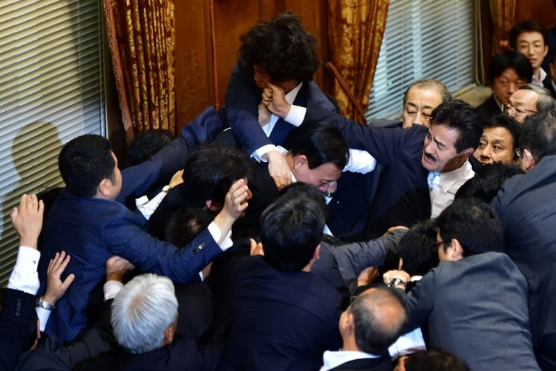 TOPSHOTS Japanese ruling and opposition lawmakers scuffle at the Upper House's ad hoc committee session for the controversial security bills at the National Diet in Tokyo on September 17, 2015. Japanese lawmakers came to blows as they tried -- and failed -- to stop the passage of a security bill that could see the military fight abroad for the first time in decades.  AFP PHOTO / Yoshikazu TSUNO