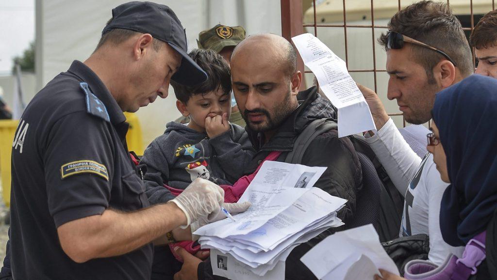 Gevgelija, 2015. szeptember 16. Görögország felõl Macedóniába érkezett illegális bevándorlók papírjait ellenõrzi egy rendõr egy regisztrációs táborban, a görög határ mellett fekvõ Gevgelija közelében 2015. szeptember 16-án. (MTI/EPA/Georgi Licovszki)