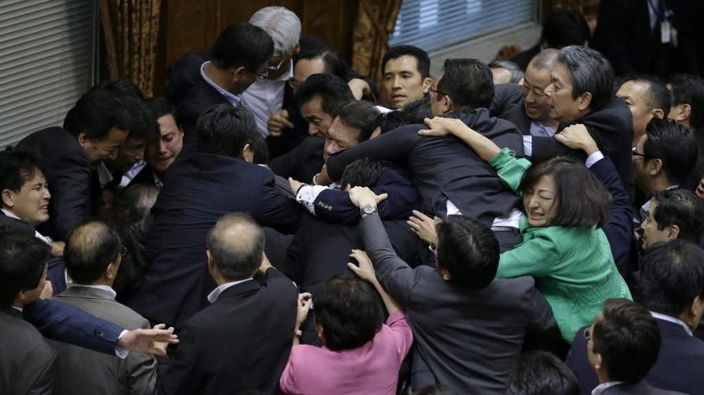 Tokió, 2015. szeptember 17.Japán kormánypárti és ellenzéki képviselők dulakodnak egy felsőházi különbizottság ülésen a parlament tokiói épületében 2015. szeptember 17-én. Az ellenzék obstrukcióval igyekszik megakadályozni egy nemzetbiztonsági törvényjavaslat felsőházi elfogadását, amely a második világháború után először engedélyezné japán katonák külföldi bevetését. (MTI/AP/Eugene Hoshiko)