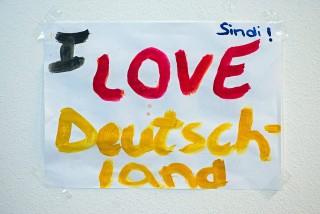 """Regensburg, 2015. szeptember 26. """"Szeretem Németországot!"""" feliratú papírlap egy befogadóközponttá alakított tornacsarnok falán a németországi Regensburgban 2015. szeptember 25-én.  (MTI/EPA/Armin Weigel)"""