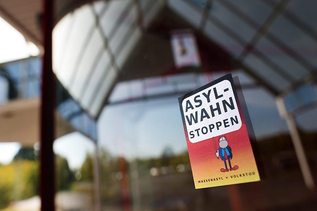 """Niederau, 2015. szeptember 26.""""Állítsátok le a bevándorlási őrületet! A tömeges bevándorlás a nemzet halála."""" felirat olvasható egy bevásárlóközpont bejáratánál elhelyezett plakáton a németországi Niederauban 2015. szeptember 25-én.  (MTI/EPA/Armin Weigel)"""