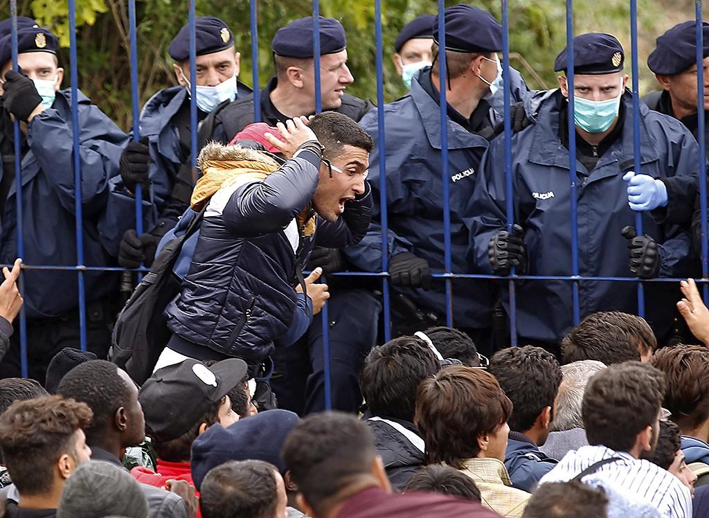 Berkasovo, 2015. szeptember 26.Horvát határőrök nyugalomra intik az illegális bevándorlókat, akik  a szerbiai Berkasovóban várakoznak arra, hogy beengedjék őket Horvátországba 2015. szeptember 25-én. (MTI/EPA/Antonio Bat)
