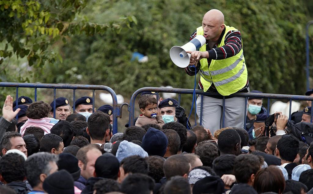 Berkasovo, 2015. szeptember 26.Egy férfi hangosbemondóval a kezében a fémkordonra mászva köszönti a horvátországi belépésre várakozó illegális bevándorlókat a szerbiai Berkasovóban 2015. szeptember 25-én. (MTI/EPA/Antonio Bat)