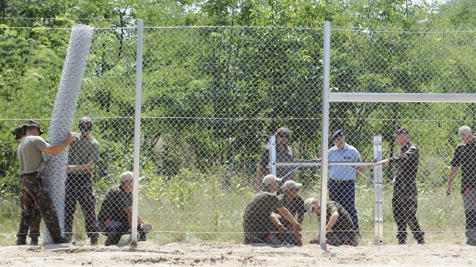 Mórahalom, 2015. július 16. Katonák és közfoglalkoztatottak dróthálót feszítenek ki a kerítésoszkopokra az ideiglenes biztonsági határzár mintaszakaszának építési munkálatai során a magyar-szerb határon, Mórahalom térségében 2015. július 16-án. MTI Fotó: Kelemen Zoltán Gergely