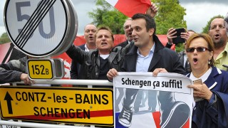 French far-right Front National (FN) party vice-president  Florian Philippot (R) and sympathizers sing the French anthem beside the road sign of Schengen after laying a wreath for the the Schengen agreements, on September 19, 2015 in Schengen, southern Luxembourg. The controls in borders were restored in several European countries further to the crisis of the migrants questioning the agreements of Schengen. AFP PHOTO / JEAN-CHRISTOPHE VERHAEGEN