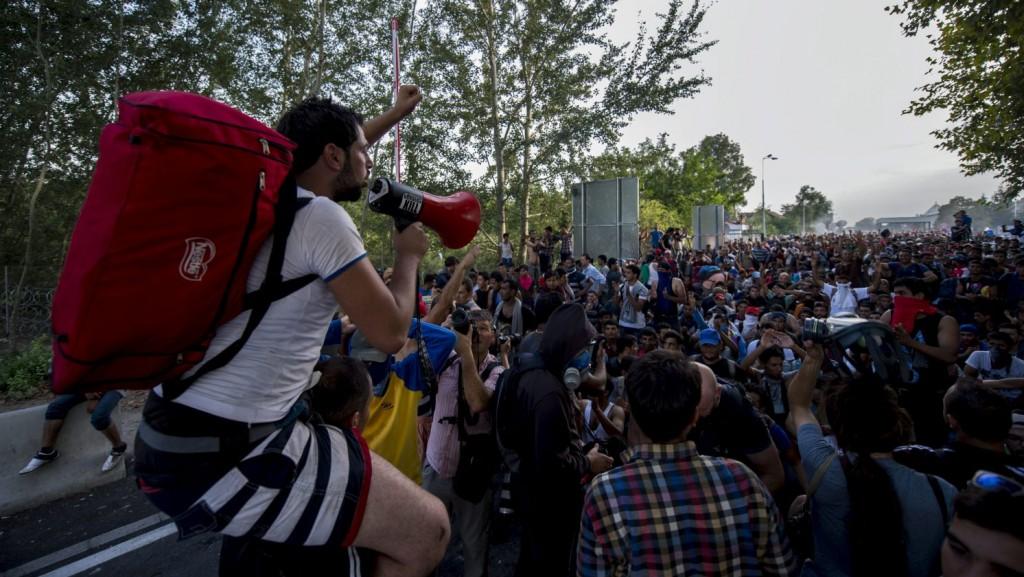 Röszke, 2015. szeptember 16. Egy migráns beszél hangosbeszélõn társa nyakában a Horgos-Röszke határátkelõhely magyar oldalán 2015. szeptember 16-án. MTI Fotó: Sóki Tamás