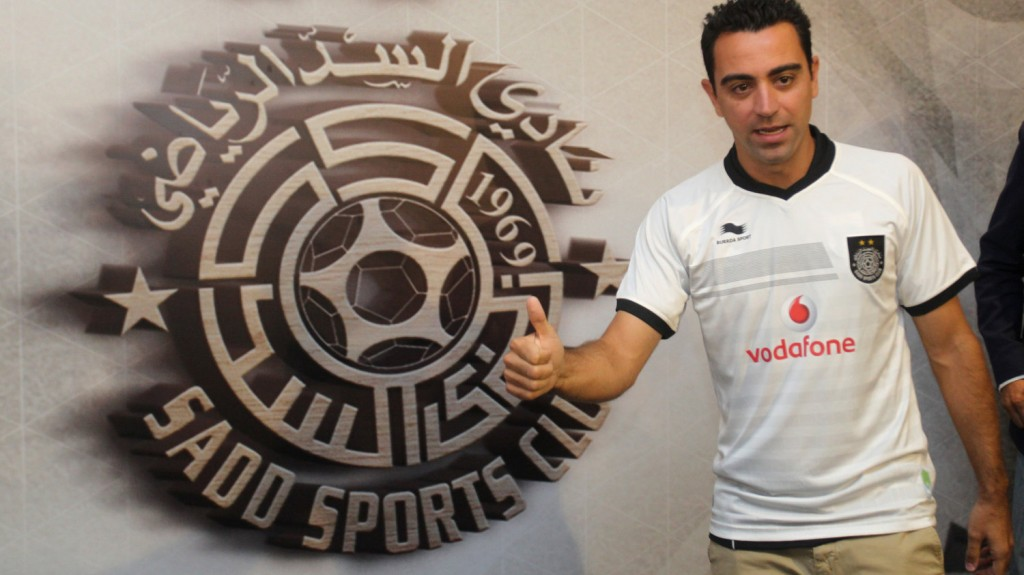 Barcelona legend Xavi Hernandez poses for a photo in his new Al-Sadd club shirt after signing a two-year contract with the Qatari team in Doha on June 11, 2015. AFP PHOTO / STR