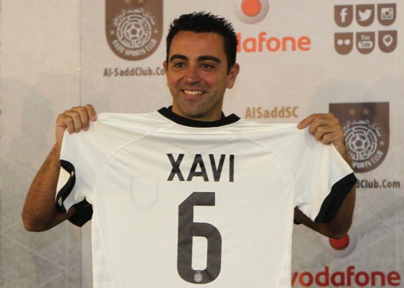 Barcelona legend Xavi Hernandez gestures in his new Al-Sadd club shirt after signing a two-year contract with the Qatari football team in Doha on June 11, 2015. AFP PHOTO / STR