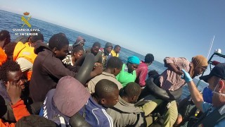 """A handout picture released on September 9, 2015 by Spanish Guardia Civil shows a group of immigrants standing on a boat during a rescue operation held by Guardia Civil close to the Alboran island off the coast of Almeria. Spanish Guardia Civil rescued on September 9, 2015, 49 sub-Saharan immigrants, 40 men, seven women and two children, when they were on a 7 meter long boat, at 2 km off the coast of the Alboran island, Almeria province.  AFP PHOTO / GUARDIA CIVIL  RESTRICTED TO EDITORIAL USE - MANDATORY CREDIT """"AFP PHOTO / GUARDIA CIVIL"""" NO MARKETING NO ADVERTISING CAMPAIGNS - DISTRIBUTED AS A SERVICE TO CLIENTS"""
