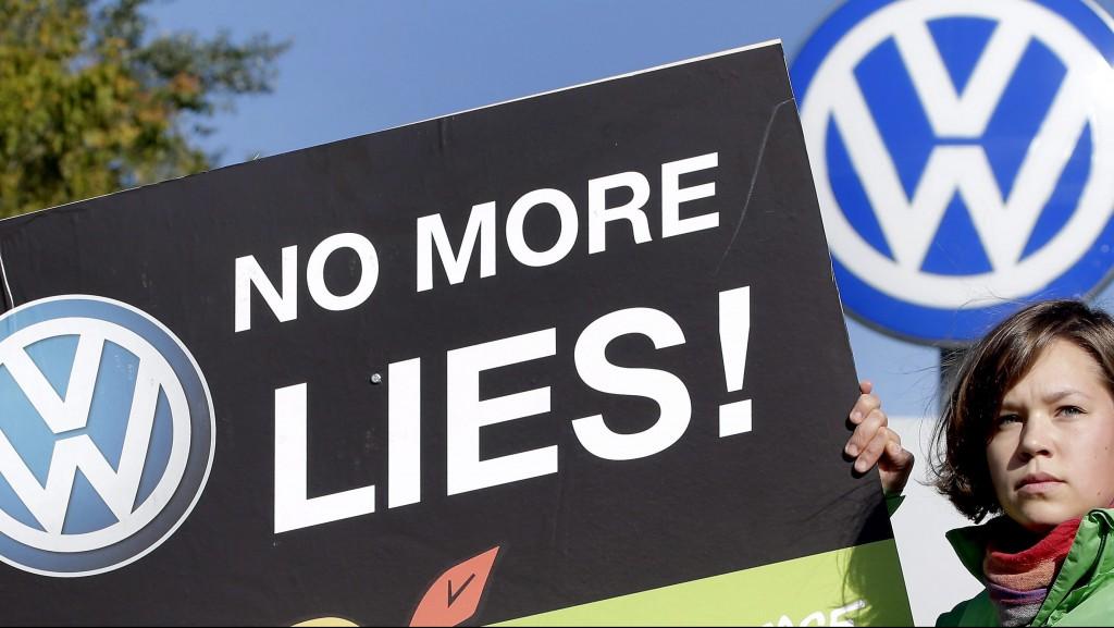 """A Greenpeace nemzetközi környezetvédõ mozgalom aktivistája egy """"Ne legyen több haugság!"""" feliratú plakáttal a Volkswagen német jármûgyártó csoport wolfsburgi gyárkapuja elõtt 2015. szeptember 25-én. Az amerikai Környezetvédelmi Ügynöksége (EPA) szeptember 18-án leleplezte a céget, hogy olyan szoftvert telepített 482 ezer dízelüzemû jármûvébe, amelynek segítségével kijátszhatók a károsanyag-kibocsátásra vonatkozó amerikai elõírások. (MTI/AP/Michael Sohn)"""